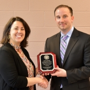 Laura Barthel presents distinguished alum plaque to Joshua Boone